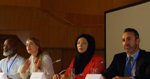 Mulher caucasiano nova que fala no orador na tabela no auditório 4k video estoque