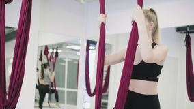 Mulher caucasiano nova que faz exercícios antigravitantes da ioga da mosca na rede filme