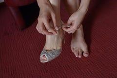 Mulher caucasiano nova que fixa o fecho de sua sandália, à vista do casamento imagens de stock