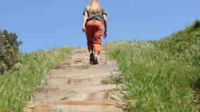 Mulher caucasiano nova que move-se para a frente para a parte superior da escada de madeira vídeos de arquivo