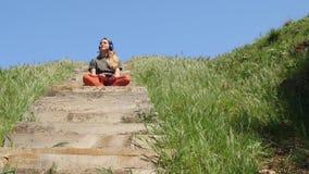 Mulher caucasiano nova que senta-se na escada de madeira e na música de escuta vídeos de arquivo