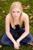 Mulher caucasiano nova que senta-se na grama, olhando acima em você Imagem de Stock Royalty Free