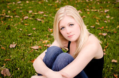 Mulher caucasiano nova que senta-se na grama que guarda joelhos Imagem de Stock Royalty Free