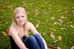 Mulher caucasiano nova que senta-se na grama que guarda Kne Imagens de Stock Royalty Free