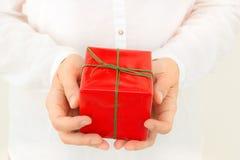 A mulher caucasiano nova realiza na caixa de presente das mãos envolvida no papel vermelho amarrado com fita verde Árvore congela foto de stock
