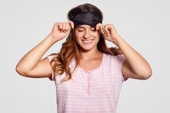 A mulher caucasiano otimista contente veste a máscara de olho, tem o sorriso largo, vestido nos pyjamas, tem a expressão feliz, v fotos de stock