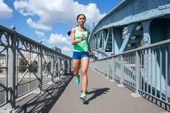 Mulher caucasiano que corre na ponte do metal Imagens de Stock