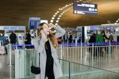 Mulher caucasiano que fala pelo smartphone e que procura o amigo no aiport Foto de Stock Royalty Free