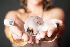 Mulher caucasiano que guarda a esfera de vidro do mundo em suas mãos Foto de Stock Royalty Free