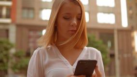 Mulher caucasiano que usa o telefone celular fora vídeos de arquivo
