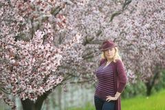 Mulher caucasiano segura com o pomar de florescência próximo longo do cabelo louro com o chapéu roxo do fedora Fotos de Stock Royalty Free