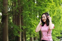 A mulher causual descuidada livre da menina da beleza aprecia relaxa o tempo no verão da mola da natureza que escuta a música fotografia de stock