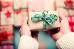 Mulher cercada por muitos presentes de Natal envolvidos, guardando o presente minúsculo belamente envolvido do vintage, ponto de  Imagens de Stock Royalty Free