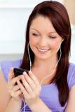 A mulher Charming escuta a música usando seu telemóvel imagem de stock royalty free