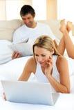 Mulher Charming que usa um portátil que encontra-se na cama fotos de stock royalty free