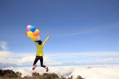 Mulher Cheering que salta com os balões coloridos no pico de montanha Fotos de Stock Royalty Free