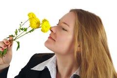 A mulher cheira flores amarelas fotos de stock royalty free