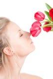 A mulher cheira o grupo de flores Imagens de Stock