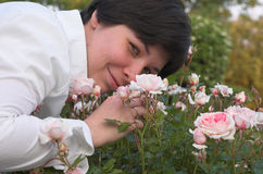 A mulher cheira rosas fotografia de stock royalty free