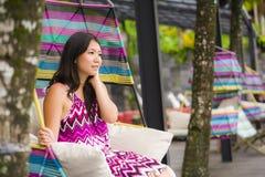 Mulher chinesa asiática bonita e feliz nova do turista que relaxa na piscina tropical do recurso luxuoso que senta-se no balanço  fotografia de stock royalty free