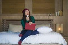 Mulher chinesa asiática bonita e feliz nova no assento do chapéu do inverno relaxado no cartão de crédito da terra arrendada da c imagem de stock
