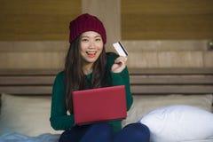 Mulher chinesa asiática bonita e feliz nova no assento do chapéu do inverno relaxado na cama que guarda o cartão de crédito usand fotografia de stock royalty free