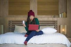 Mulher chinesa asiática bonita e feliz nova no assento do chapéu do inverno relaxado na cama que guarda o cartão de crédito usand imagem de stock