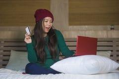 Mulher chinesa asiática bonita e feliz nova no assento do chapéu do inverno relaxado na cama que guarda o cartão de crédito usand foto de stock royalty free
