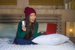 Mulher chinesa asiática bonita e feliz nova no assento do chapéu do inverno relaxado na cama que guarda o cartão de crédito usand imagem de stock royalty free
