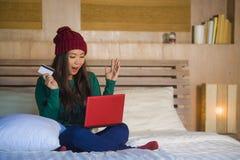 Mulher chinesa asiática bonita e feliz nova no assento do chapéu do inverno relaxado na cama que guarda o cartão de crédito usand foto de stock