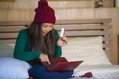 Mulher chinesa asiática bonita e feliz nova no assento do chapéu do inverno relaxado na cama que guarda o cartão de crédito usand imagens de stock