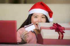 Mulher chinesa asiática bonita e feliz nova que veste o chapéu de Santa que guarda a caixa do cartão de crédito e do presente de  foto de stock