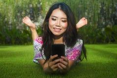 Mulher chinesa asiática bonita e lindo atrativa nova que encontra-se no parque da grama verde usando os meios sociais app do Inte fotos de stock royalty free