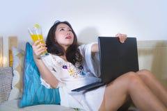 Mulher chinesa asiática bonita e pensativa que bebe o sofá relaxado de encontro do sofá da sala de visitas do suco de laranja sau imagens de stock