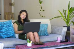 Mulher chinesa asiática bonita e relaxado nova no seu assento 20s ou 30s feliz no sofá do sofá da casa da sala de visitas que tra Imagem de Stock