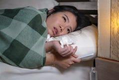 Mulher chinesa asiática cansado e doente bonita nova que encontra-se no doente da cama em casa que sofre a gripe fria e a tempera imagens de stock