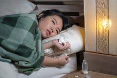 Mulher chinesa asiática cansado e doente bonita nova que encontra-se no doente da cama em casa que sofre a gripe fria e a tempera imagem de stock royalty free