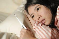Mulher chinesa asiática cansado e doente bonita nova que encontra-se no doente da cama em casa que sofre o sentimento frio da gri foto de stock