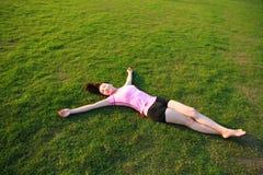 A mulher chinesa asiática da aptidão tem um resto na grama em um parque Imagem de Stock