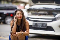 Mulher chinesa asiática no esforço encalhada na falha no motor de sofrimento do carro da rua que tem o problema do mecânico que c imagem de stock