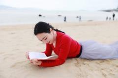 A mulher chinesa asiática nova leu o encontro em seu lado no livro de leitura da areia na praia fotos de stock royalty free