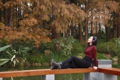 A mulher chinesa asiática nova que escuta a música com fones de ouvido senta-se sob a árvore fotos de stock royalty free