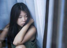 Mulher chinesa asiática triste e deprimida nova que olha pensativa com a dor e a depressão de sofrimento do vidro de janela no co Fotografia de Stock