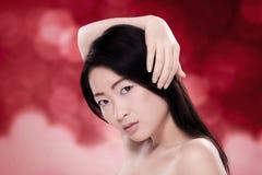 Mulher chinesa bonita com cabelo saudável contra o fundo vermelho borrado Foto de Stock Royalty Free