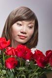 Mulher chinesa bonita e rosas vermelhas Fotografia de Stock Royalty Free