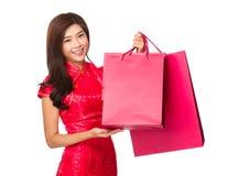 Mulher chinesa com o saco de compras do cheongsam e da posse Fotografia de Stock Royalty Free