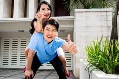 Mulher chinesa e homem que apreciam a casa nova Fotografia de Stock Royalty Free