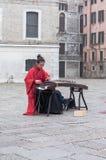 A mulher chinesa está jogando um instrumento tradicional em um quadrado, a emoção de sua música é tristeza imagem de stock