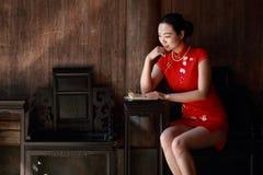 A mulher chinesa feliz no cheongsam vermelho leu o livro imagens de stock royalty free