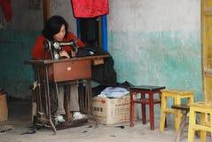 Mulher chinesa no trabalho em uma loja dos vestuários foto de stock